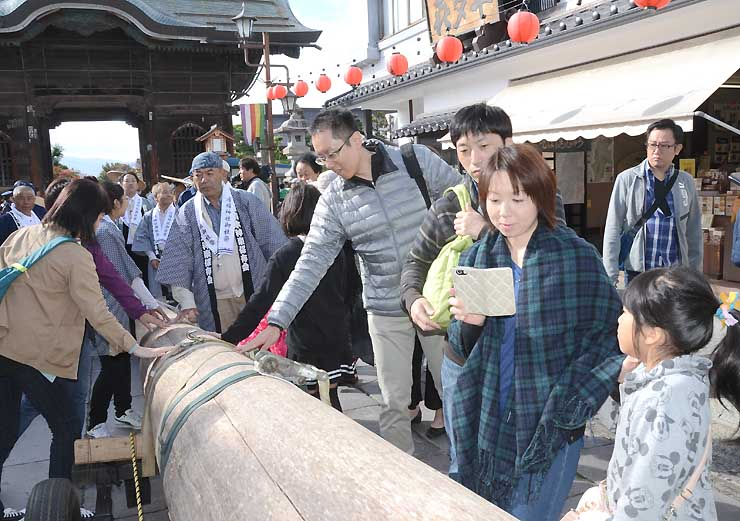 善光寺参道を曳行した一之柱に触れたり、記念撮影をしたりする観光客ら
