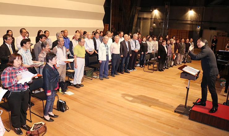 垣内さん(右)の指導を受ける団員たち=高岡市民会館
