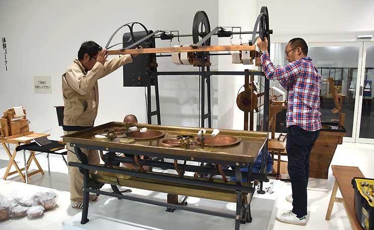 岡谷蚕糸博物館に展示されているフランス式繰糸機の復元機を運び出す映画製作スタッフら=13日午後5時20分、岡谷市