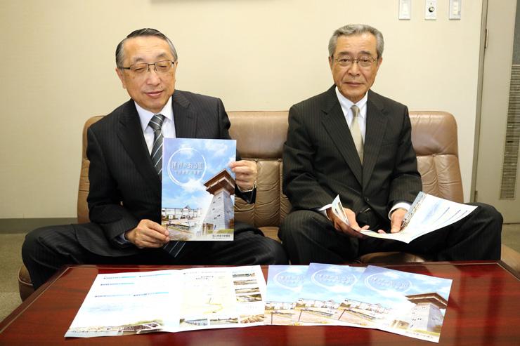 富山港運河愛護会が作製したパンフレットを紹介する金尾会長(左)と網谷吉博副会長=富山市東岩瀬町