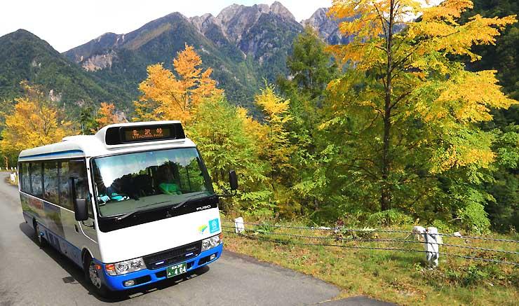 南アルプス鋸岳(中央)を背に色づき始めた紅葉の中を走る南ア林道バス=14日、伊那市長谷
