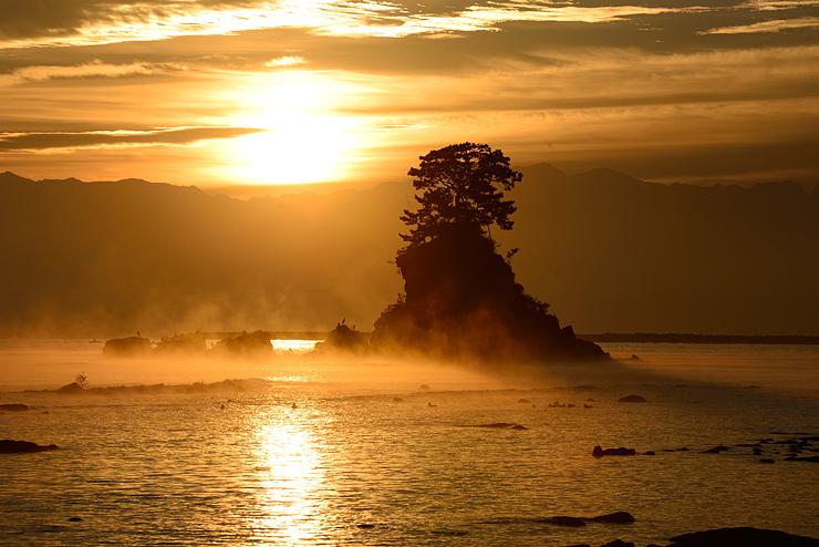 朝日に照らされ、女岩を背景に立ち上がる気嵐=14日午前6時15分ごろ、高岡市の雨晴海岸(愛甲喜一郎さん撮影)