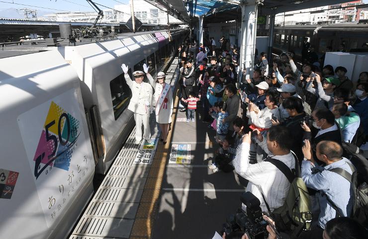 50周年記念エンブレム(左)が貼られた特急あずさの車両。大勢の鉄道ファンらが見守る中、出発した=15日、松本駅