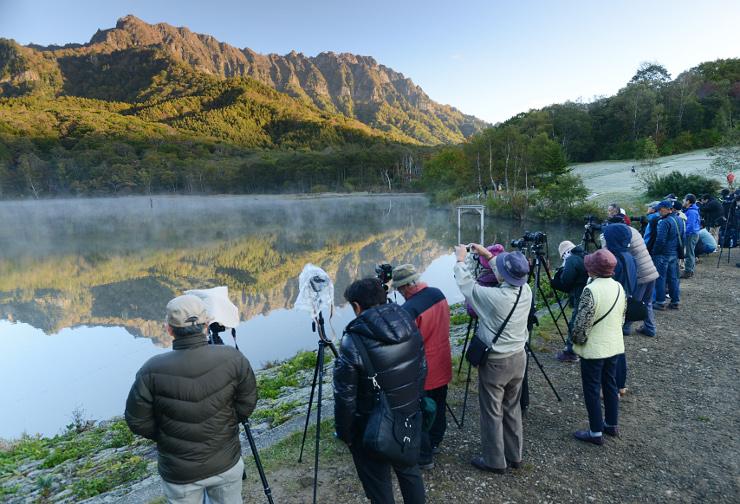 水面に水蒸気が漂う鏡池で早朝から撮影を楽しむ写真愛好家ら=15日午前6時26分