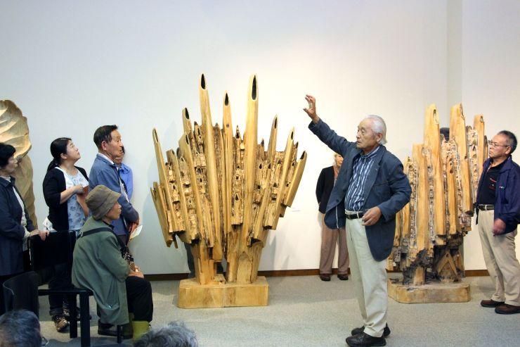 開館20周年となった「星と森の詩美術館」で、身ぶりを交えながら、作品の説明をする藤巻秀正さん=十日町市稲葉