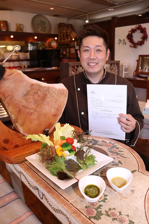 最優良レストランの通知書を手に、サルーミを使った料理を見せる村中さん