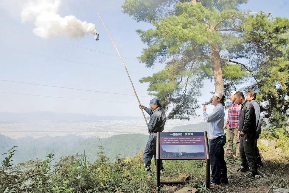 一乗谷城跡でのろしを上げる朝倉氏遺跡保存協会のメンバー=16日、福井市の一乗城山