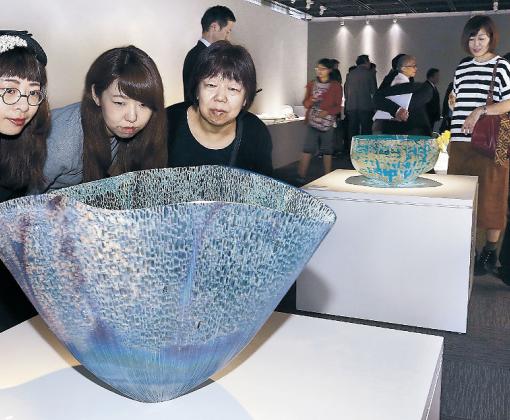 ガラスの可能性を感じさせる作品に見入る来場者=19日午前10時10分、金沢市のしいのき迎賓館