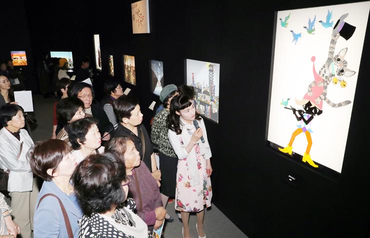マイクを手にした亜季さん(右)のギャラリートークで作品を鑑賞する大勢の入場者=県立近代美術館