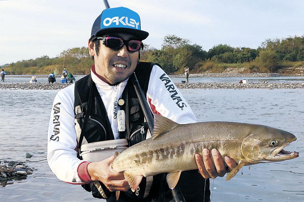 第1号を釣り上げた北野さん=白山市の手取川右岸