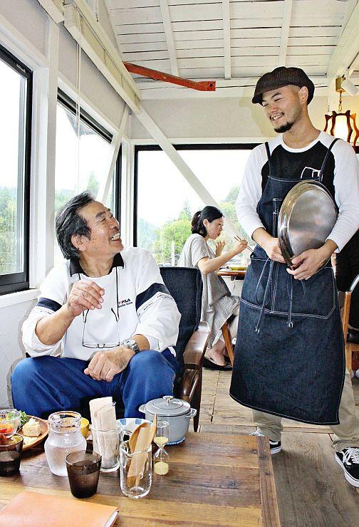 「イーリーカフェ」を訪れた客と談笑する矢島衛さん(右)=柏崎市石曽根