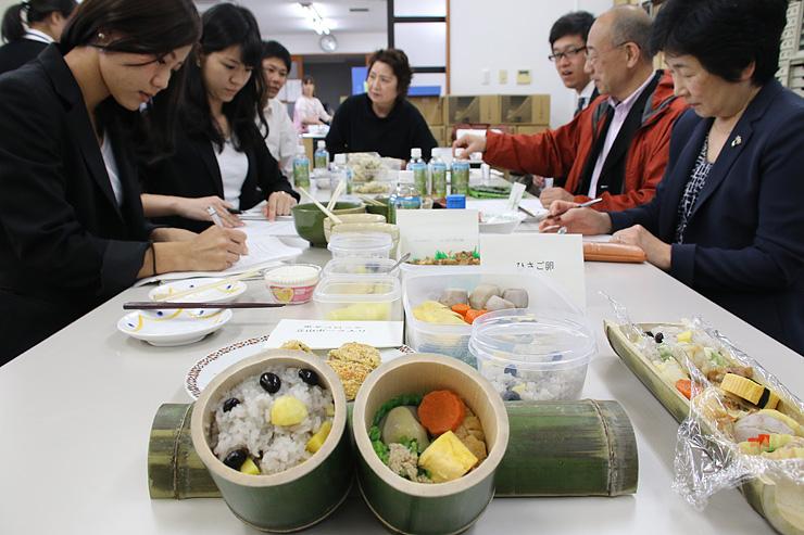 竹の容器を使った弁当を試作し、意見を交わす関係者