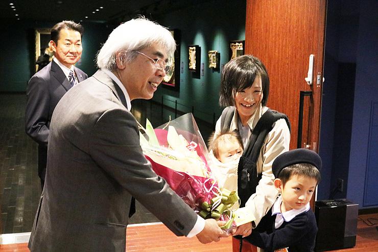 片岸館長(手前左)から花束を受け取る鈴木さん=ギャルリ・ミレー