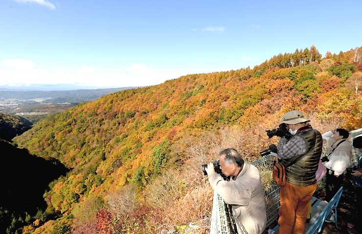 茅野市の横谷観音展望台から眺めを楽しむ人たち=26日