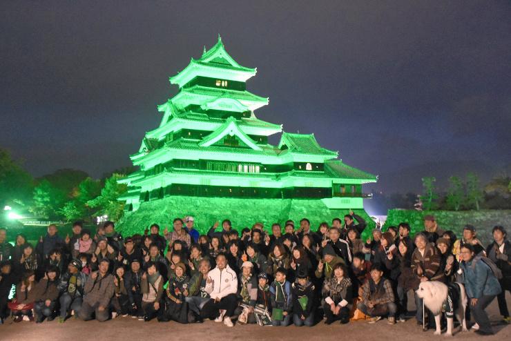 緑色にライトアップされた松本城を背に記念撮影する松本山雅のサポーターら=29日午後5時半すぎ、松本市