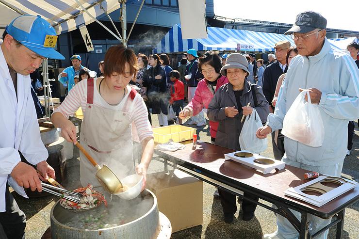 来場客でにぎわい、列ができた大漁鍋のコーナー=ひみ漁業交流館魚々座前
