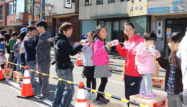 チェーンクロス乾杯し、おやべミルクセーキを飲む小野さん(右から3人目)ら参加者=石動駅前商店街