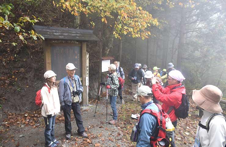 青崩峠の案内板の前で記念撮影する参加者たち