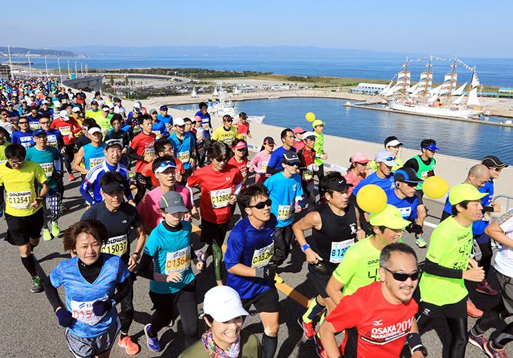 帆を張った海王丸や富山湾の景色を楽しみながら新湊大橋を駆け抜けるマラソン参加者=射水市海王町