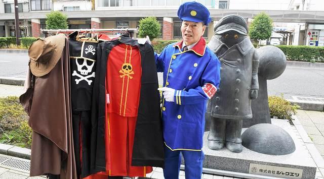 銀河鉄道999の衣装の無料貸し出しを企画した田保さん。バックに立つ像はキャラクターの「車掌」=31日、福井県敦賀市