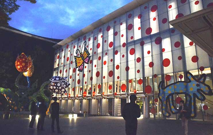 ライトアップで外壁に浮かび上がった草間さんの作品「松本から未来へ」=松本市美術館