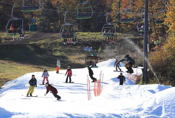 紅葉した木々に囲まれたゲレンデで初滑りを楽しむ来場者たち=3日午前9時5分、軽井沢町
