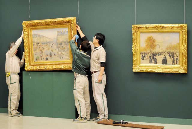 ピサロの作品を慎重に設置するスタッフ=3日、福井市の福井県立美術館