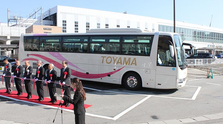 観光バス駐車場の完成を祝い、テープカットする関係者=富山駅の「南西街区」