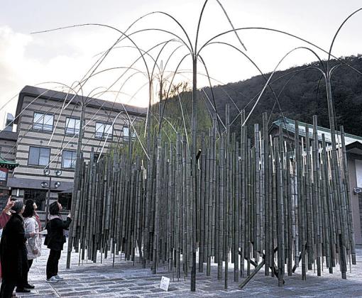 竹を用いた大作に見入る来場者=加賀市山中温泉の山中座前広場