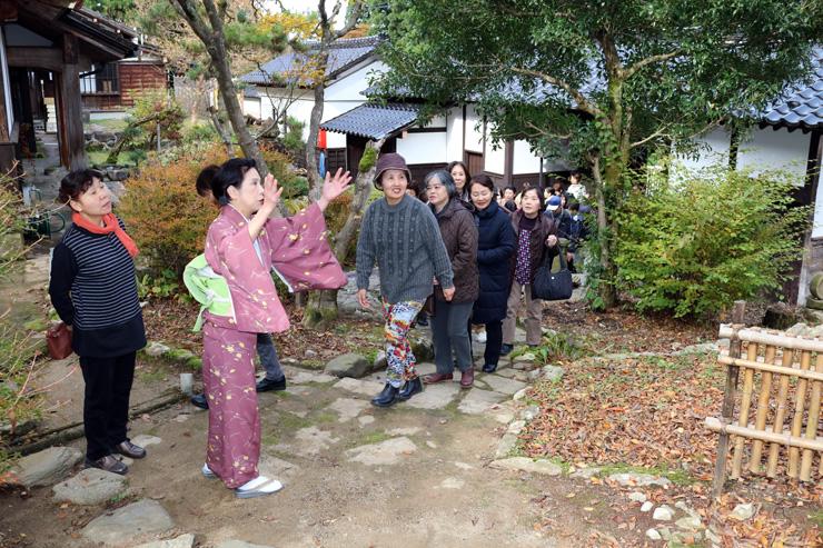 関口さん(手前左から2人目)の案内を聞きながら見学する参加者=烏帽子山荘
