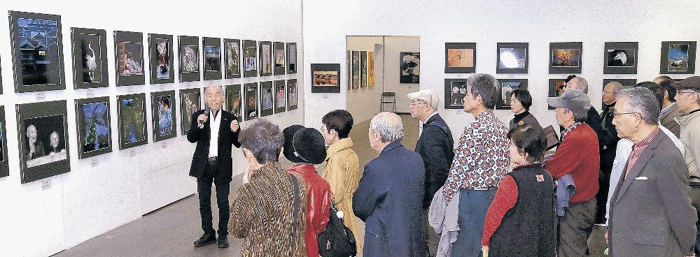 写真部門の作品解説を聞く来場者=金沢21世紀美術館