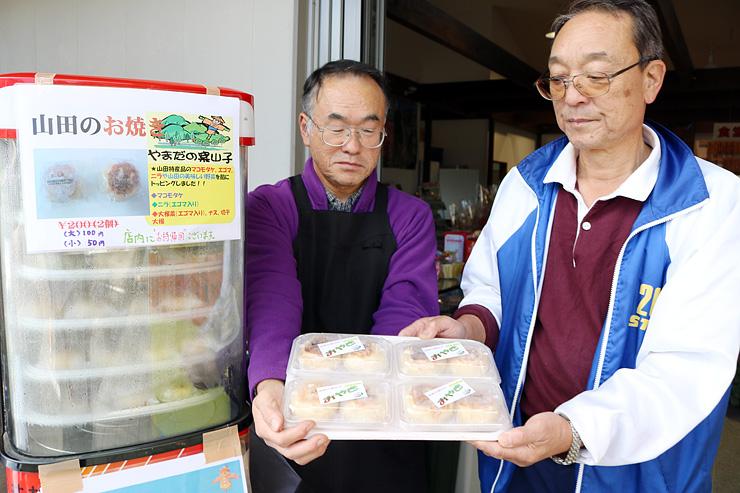 山田地域産の食材を使ったおやきを持つ若林理事長(右)ら