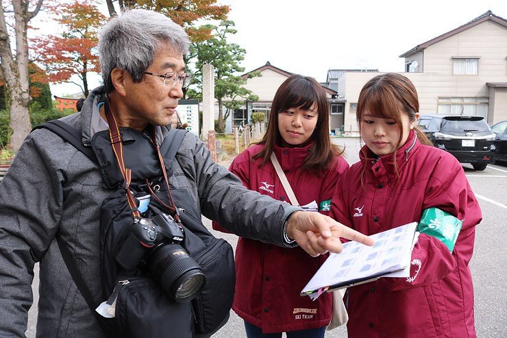 観光客(左)にアンケート調査を行う学生