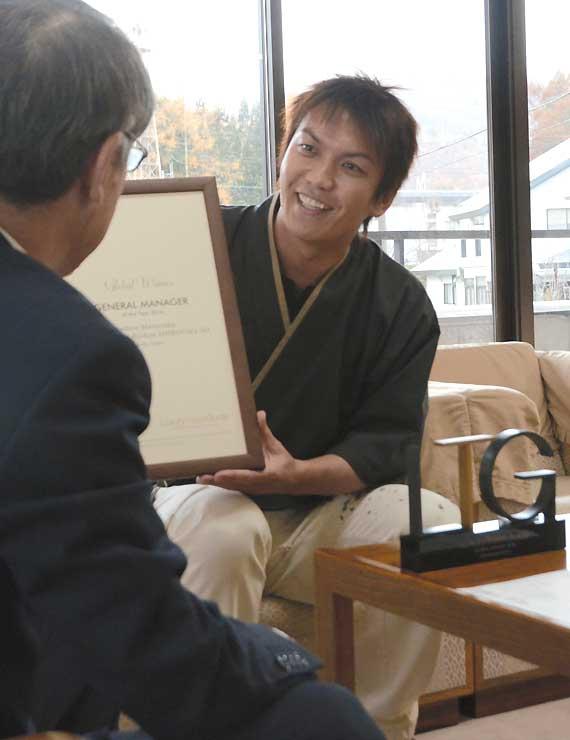 下川村長(左)にロンドンの受賞式で受け取った賞状とトロフィー(右)を見せる丸山さん