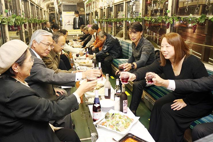 ワイングラスを片手に、笑顔で乾杯する乗客=万葉線車内