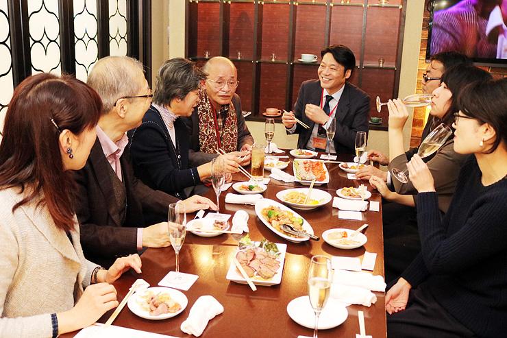 おいしい料理を味わいながら語らう野村さん(左から5人目)と参加者=ハリーズ・ザ・コーヒーバル