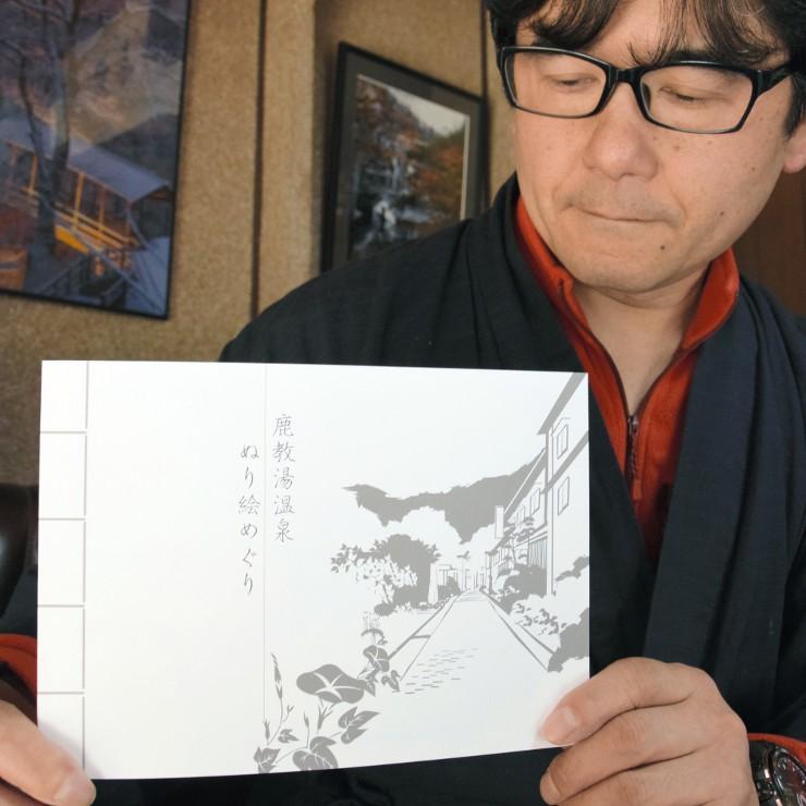 塗り絵帳を手にする斎藤さん。好きな画材で自由に塗り絵を楽しめる