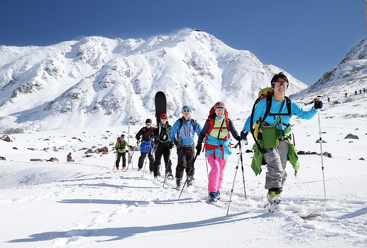 雄山(奥)など立山連峰の雄大な景色を眺めながらスキーを楽しむ人たち=立山・室堂