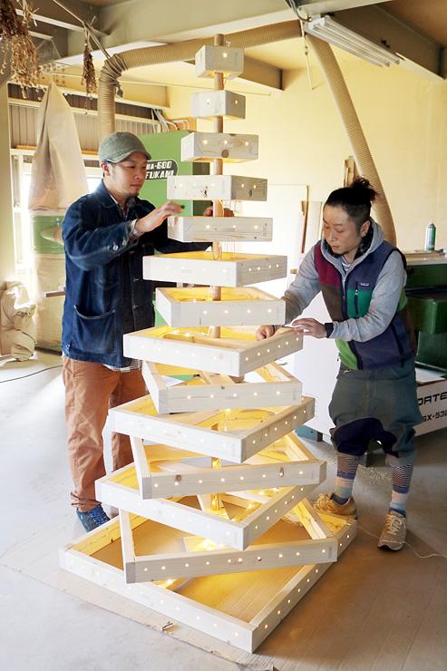協力してクリスマスツリーを仕上げる伊藤社長(右)と山田代表=家具工房チボリ