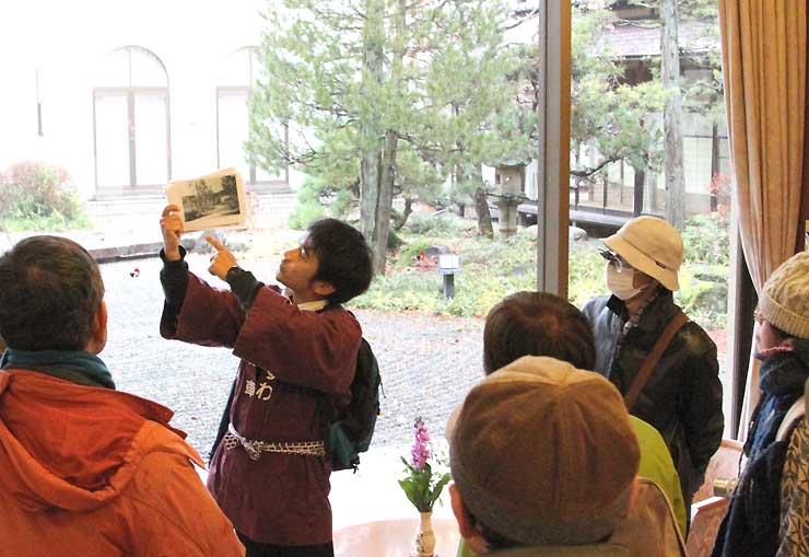 諏訪湖ホテル「菊の間」(右奥)を見ながら横溝が住んでいた頃の諏訪を紹介する渡辺さん(中央)