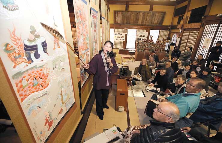 西光寺の竹沢さん(中央)から地獄絵の絵解きを聞く富山県立山博物館の関係者ら=30日、長野市