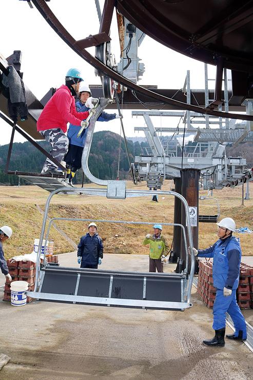 ワイヤに搬器を取り付ける作業員=立山山麓スキー場極楽坂エリア