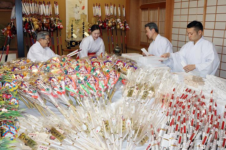 縁起物の準備作業を進める藤井宮司(奥左)ら=高瀬神社