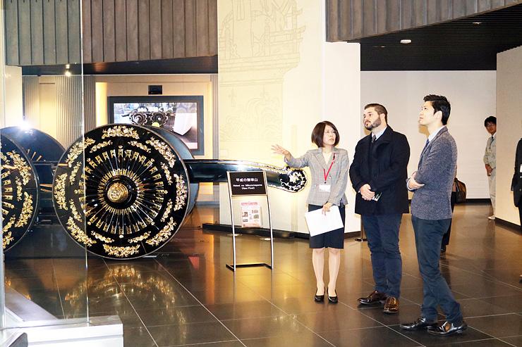 高岡御車山会館で山車について説明を受けるモレリ社長(左から2人目)