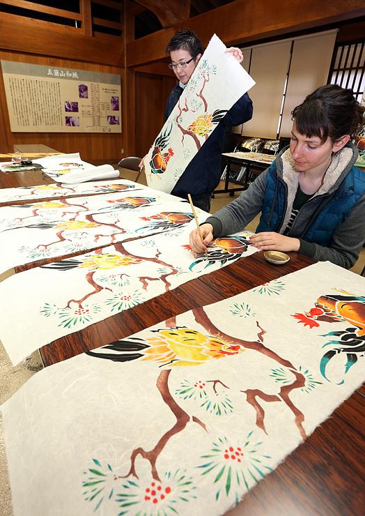 ニワトリをデザインした和紙タペストリーを作るブルースタールさん(右)ら=五箇山和紙の里
