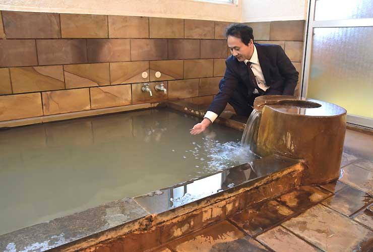 日帰り利用を始めた「旭湯温泉」に手を漬ける佐久ホテルの篠沢社長