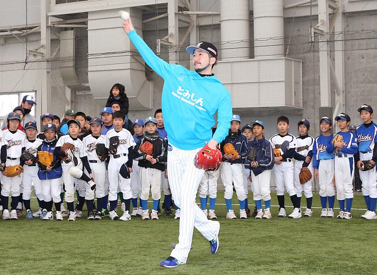 児童に正しいキャッチボールを指導する石川投手=県総合運動公園