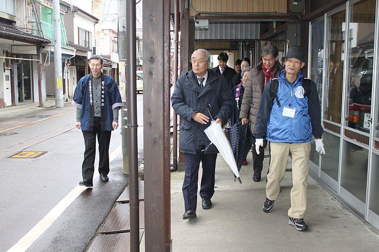 高田駅前の雁木通りを散策するガイド役の住民ら=13日、上越市