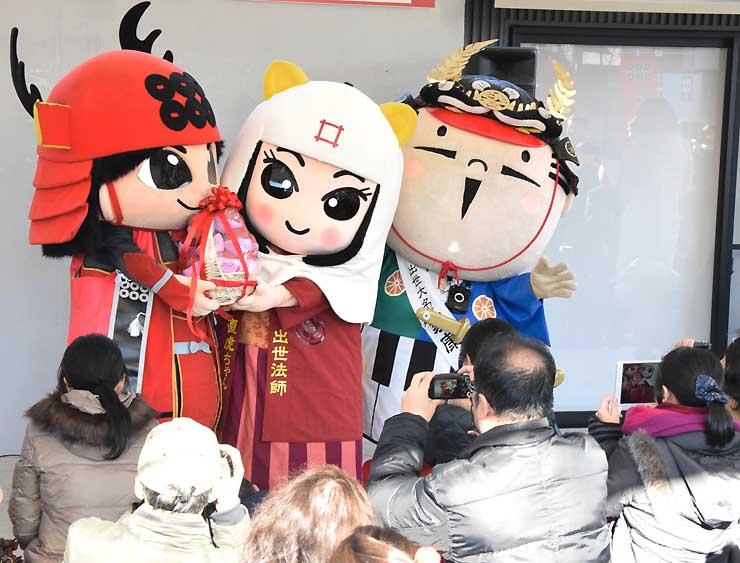 ご当地キャラクターが交流するイベントで、「出世法師直虎ちゃん」(中央)に信州産リンゴを贈る「真田幸丸」。右は「出世大名家康くん」。