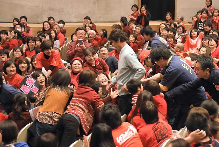 草刈正雄さん(中央)の登場に盛り上がるパブリックビューイングの会場=18日午後7時21分、上田市の丸子文化会館セレスホール
